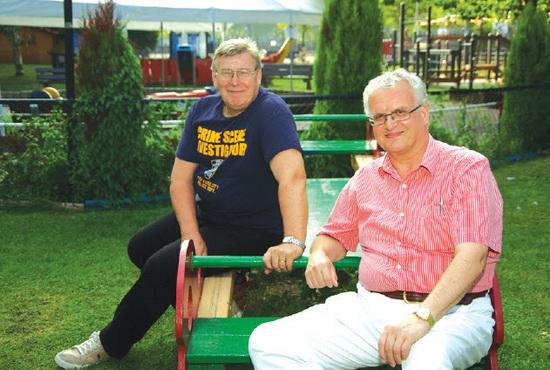 """Historicus Dik Vuik, rechts en Willem van Bracht, voorzitter van Speeltuinvereniging Crooswijk, hebben elkaar gevonden voor het typisch Crooswijkse evenement genaamd het 'Schuttersfeest'. op de gewijde grond van het Schuttersveld. Dikwerkt hiervoor overigens ook samen met de plaatselijke kunstenaars Willem van Hest en Ron Blom. Dik: """"De schutters van vroeger zijn de actieve bewoners van nu"""". De Crooswijkse speeltuin dient als 'uitvalbasis' voor de vele activiteiten tijdens het Schuttersfeest. Centraal in het Schuttersfeest staat de 'wijkmarkt' waar de bezoekers kennis kunnen nemen van de vele, plaatselijke bewonersinitiatieven. De bedoeling daarvan zal duidelijk zijn. Het Schuttersfeest aanstaande zondag móet een succes worden, want dan kunnen de Tamboers en Pijpers (Marinierskapel) het volgend jaar misschien ook worden uitgenodigd, hoopt Dik."""