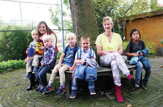 Maandag 1 september, voor 't eerst opgehaald van hun scholen, van links naar rechts, Olivier, Max, Tijmen, Quinten en Xayden. Ze werden opgevangen door Melanie van Dijk, leidster van de nieuwe NSO-groep 'Pluto', links, en Laura Veenema, locatie-manager NSO de Speeltuin.