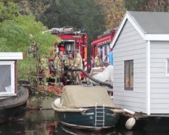 Duikers dichten lekkage in zinkende woonboot aan Crooswijksebocht